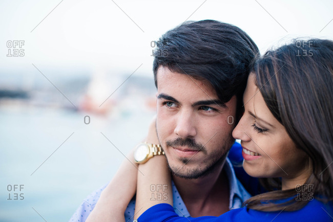 Charming woman in blue dress in embrace with handsome man bonding on pier of city port with ship on background