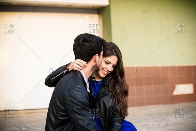 Loving man and woman in elegant clothes kissing on street background
