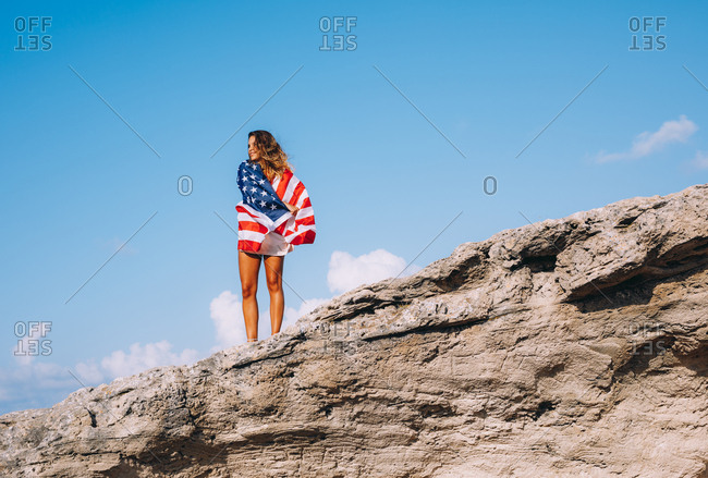 Cheerful tanned woman on vacation in casual while shirt standing on big cliff and holding American flag under hand with blue sky and rocked obelisk on background