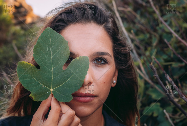 Peaceful young woman relaxing in nature while covering half face with green leaf of fig and looking at camera