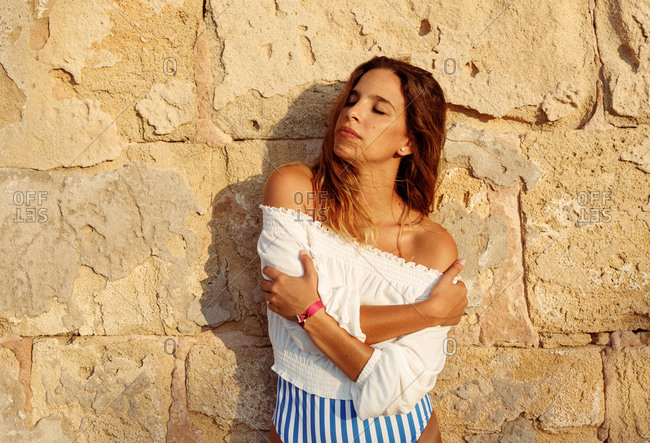 Tranquil female traveler in white blouse enjoying in vacation while standing and wrapping oneself in arms with rocked wall on background
