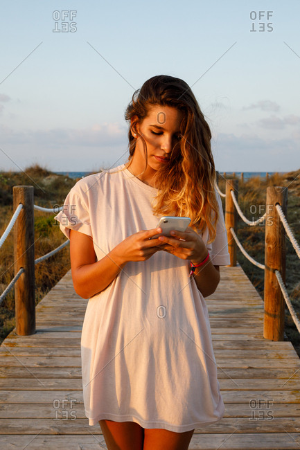 Pensive long haired woman surfing mobile phone while walking on suspension bridge in sunlight