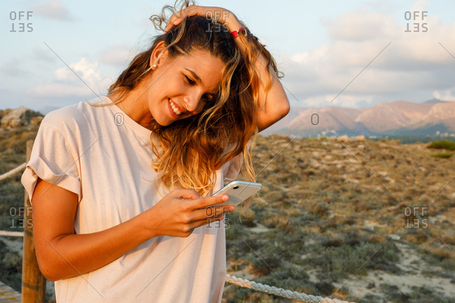 Satisfied curly haired female traveler in casual white shirt touching hair while web surfing on mobile phone with beautiful landscape on background