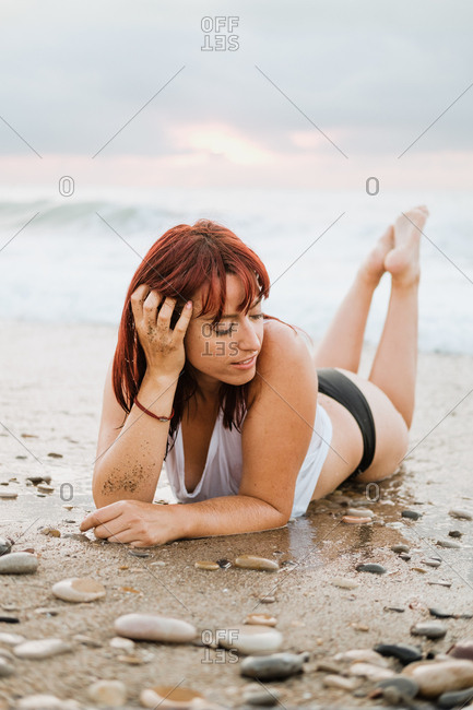 Relaxed redhead peaceful lady in underwear lying down on beach with stones on tropical coast