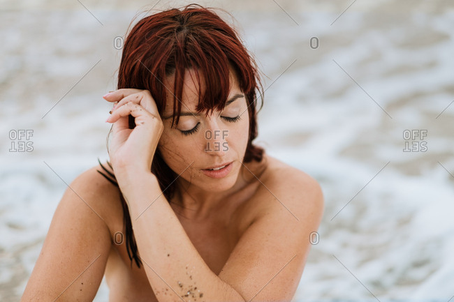 Young nude free calm female posing with closed eyes while sitting in a rocky beach