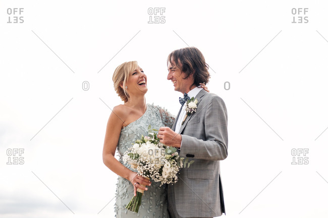 Pleased young groom in wedding suit proudly looking at beautiful blonde haired bride in stylish dress behind at empty sandy seashore