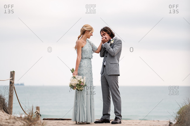 Pleased young groom in wedding suit kissing hand of blonde haired bride in stylish dress behind at empty sandy seashore
