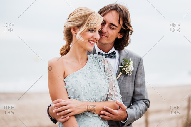 Pleased young groom in wedding suit hugging blonde haired bride in stylish dress behind at empty sandy seashore
