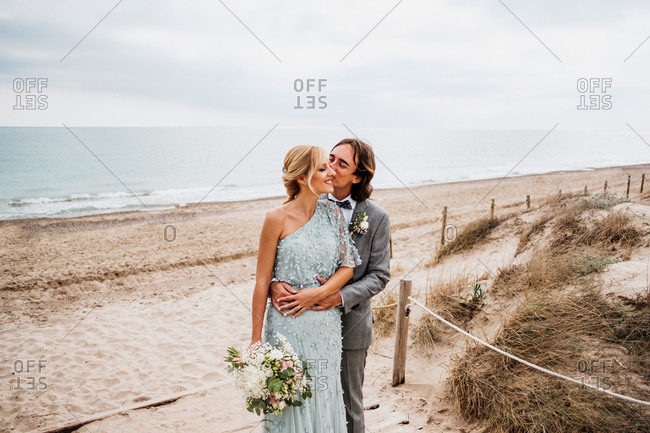 Pleased young groom in wedding suit hugging and kissing blonde haired bride in stylish dress behind at empty sandy seashore