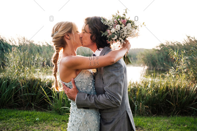 Stylish newly married couple in wedded suits embracing and kissing with green plants and mere on sunny day