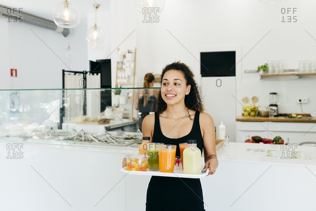 Cheerful waitress serving healthy drinks for friends