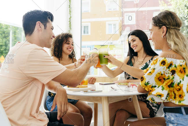 Diverse friends clinking glasses with smoothies