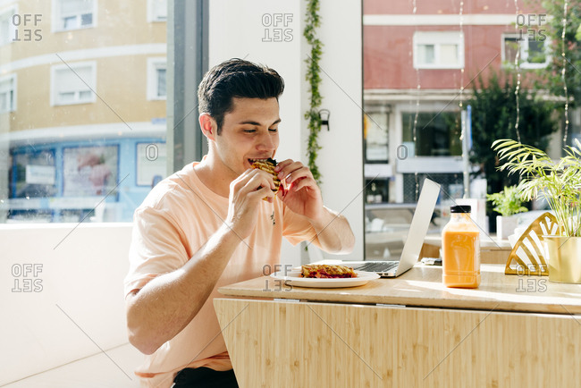Happy young man with closed eyes biting sweet snack while sitting at table with laptop against window in restaurant