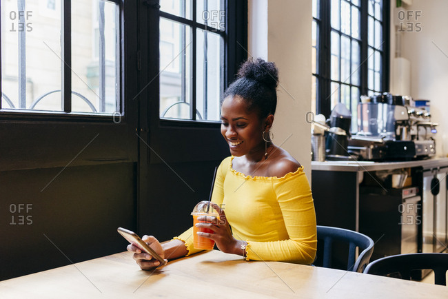 Attractive smiling African American female in bright yellow blouse holding disposable cup of fruit juice and browsing internet on smartphone while sitting at table in cafe