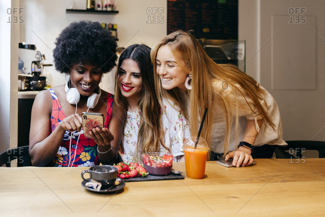 Female friends look over the photos they took over breakfast