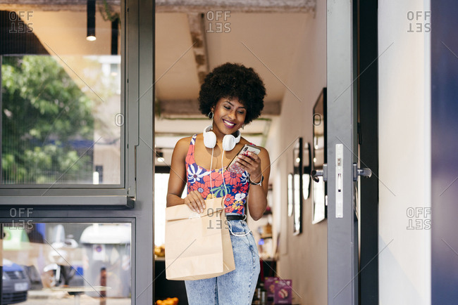 Pretty young black female with headphones on her neck leaves a restaurant with leftovers