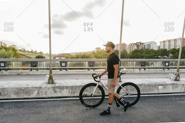 Side view of young casual bearded male cyclist in black cap walking with bike on road with city buildings on background
