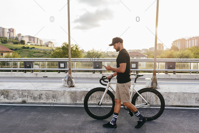 Side view of young casual bearded male cyclist in black cap using phone while walking with bike on road with city buildings on background