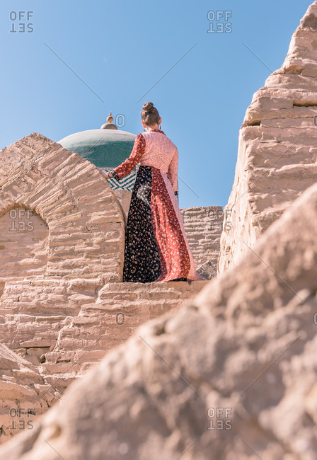 From below back view of calm female in traditional long dress standing on stone stairs and looking away against old blue dome of mausoleum of Pahlavan Mahmud in Khiva