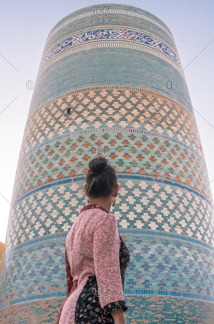 From below back view of lady in traditional clothes standing alone and looking at incomplete round tower of Kalta Minor minaret with colorful glossy brick wall on street in Khiva