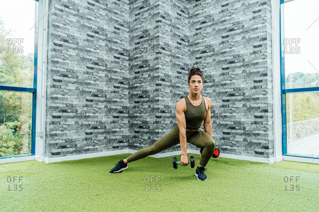 Full body fit lady in sportswear performing lunges with dumbbells while exercising in corner of modern gym