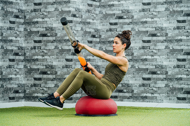 Excited slim female in sportswear sitting on balance trainer and exercising with tube with liquid during training in gym