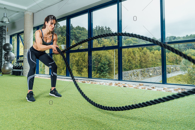 Full length focused strong woman in sportswear doing exercise with battle ropes during training in modern gym