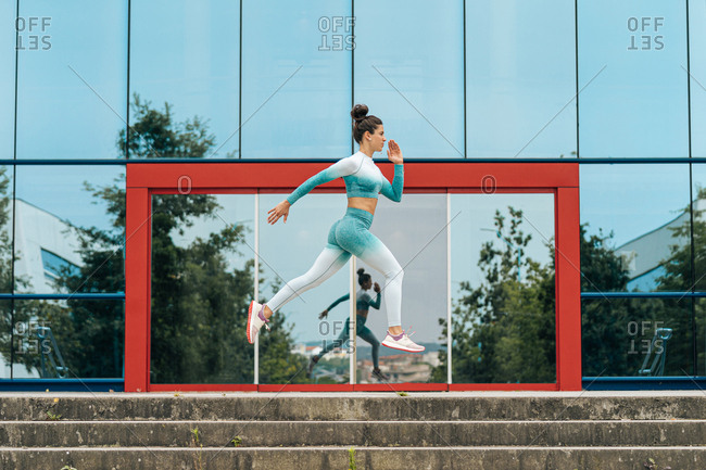 Focused female in sportswear running fast towards camera while training on asphalt road with glass building on the background