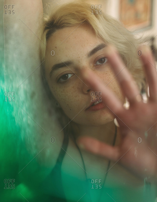 Through glass pensive young blond freckled female with brown eyes looking at camera and dreaming while touching transparent surface with green transition