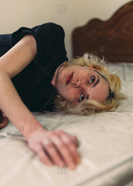 Pretty young blond freckled female with brown eyes in casual black shirt looking away and contemplating while resting in bed