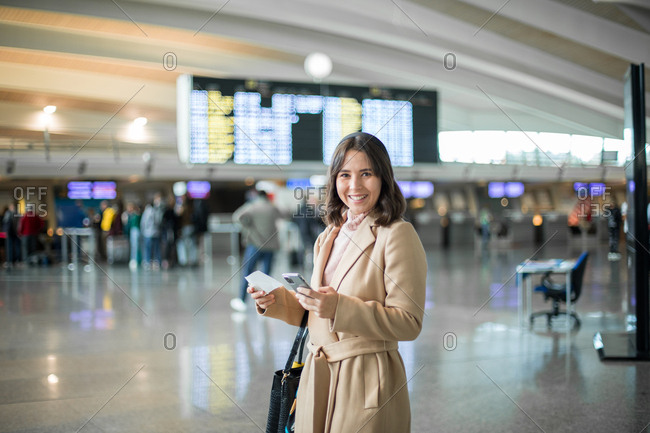 Woman using smartphone at airport