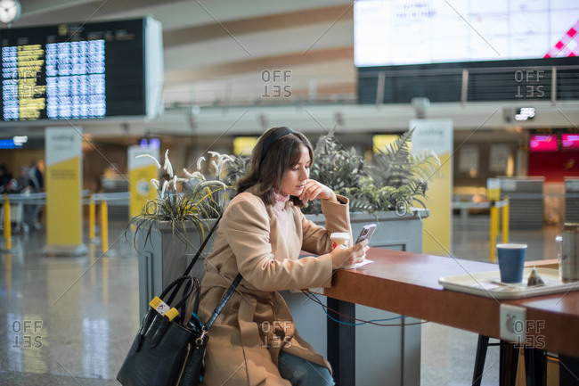 Lady sitting and using smartphone at airport