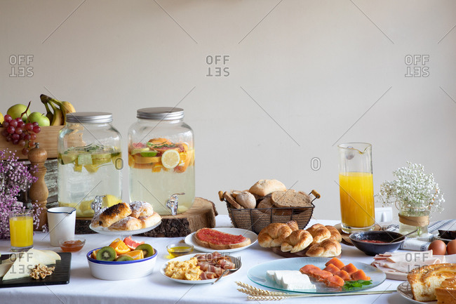 From above of appetizing sitting table for breakfast with bakery seafood sandwiches eggs and orange juice at stylish dinning room