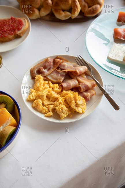 From above of delicious dish of bacon and coddled eggs on plate with fork on beautiful breakfast table