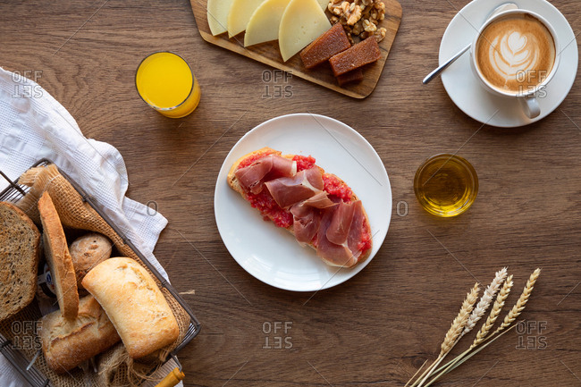 From above of tasty Spanish toast with tomato and bacon for breakfast on wooden table