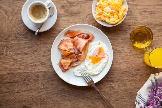 From above fresh fried eggs with bacon in plate served on table with juice and coffee for breakfast