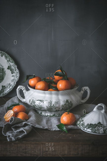 Sophisticated still life with ripe orange tangerines with green leaves in deep white bowl on table on gray background