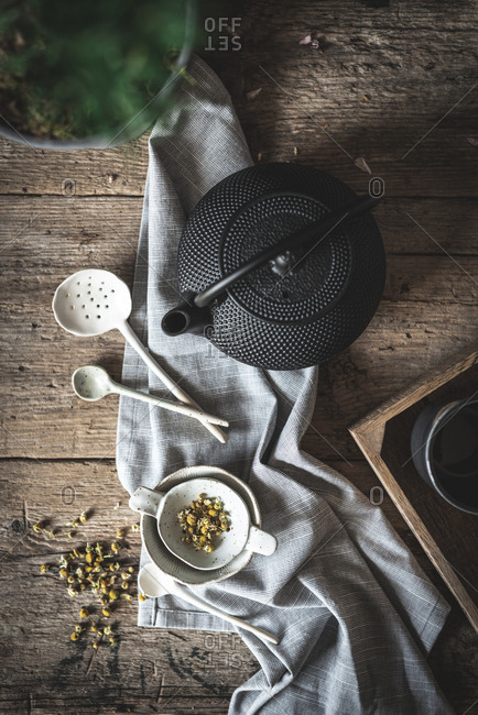 From above composition of black teapot and white bowl and chamomile herbs on wooden table