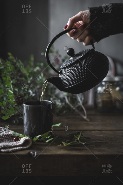 Round black teapot in hand of crop person pouring chamomile tea in black mug on wooden table decorating with green leaves