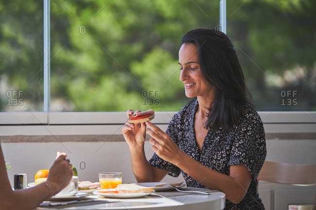 Side view of smiling hungry woman with hairstyle sitting at served table and eating sandwich with crop person in light room in Mallorca, Spain