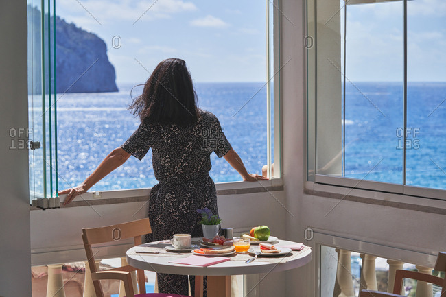 Back view of thoughtful unrecognizable woman standing nearby window enjoying shiny calm water in light cozy terrace with served for breakfast table in Mallorca, Spain
