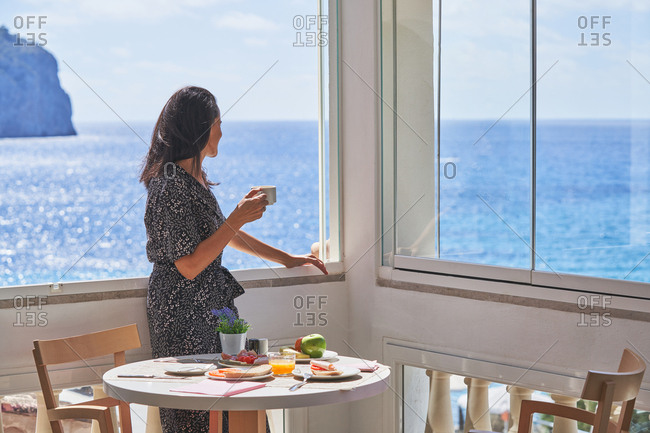 Side view of thoughtful woman drinking coffee standing nearby window enjoying shiny calm water in light cozy terrace with served for breakfast table in Mallorca, Spain