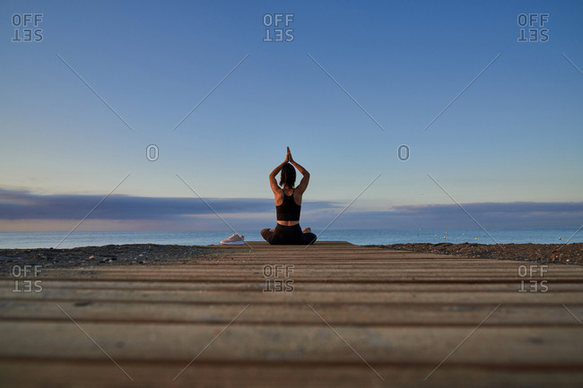 Back view female with crossed legs and meditating while sitting on seashore against cloudy evening sky