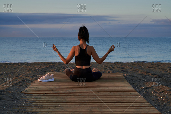 Positive female with crossed legs sitting on seashore against cloudy evening sky