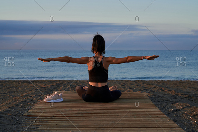 Back view of fit female in sportswear stretching out arms while sitting crossed legged near sea and doing yoga in evening