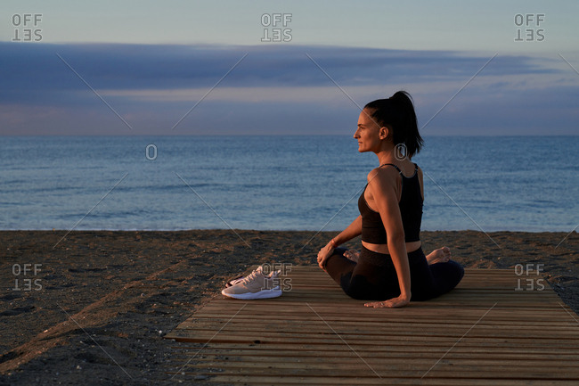 Back view of flexible female twisting body while sitting crossed legged on seashore and doing yoga in evening