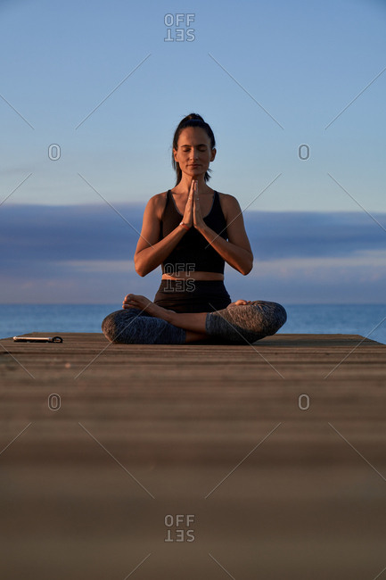 Positive female with crossed legs and clasped hands smiling and meditating while sitting on seashore against cloudy evening sky