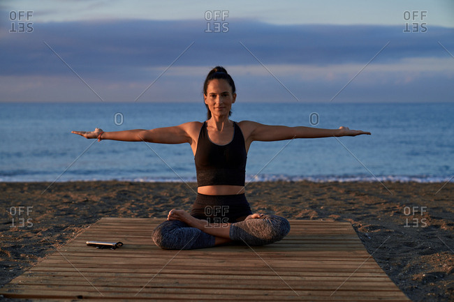 Positive female with crossed legs meditating while sitting on seashore against cloudy evening sky