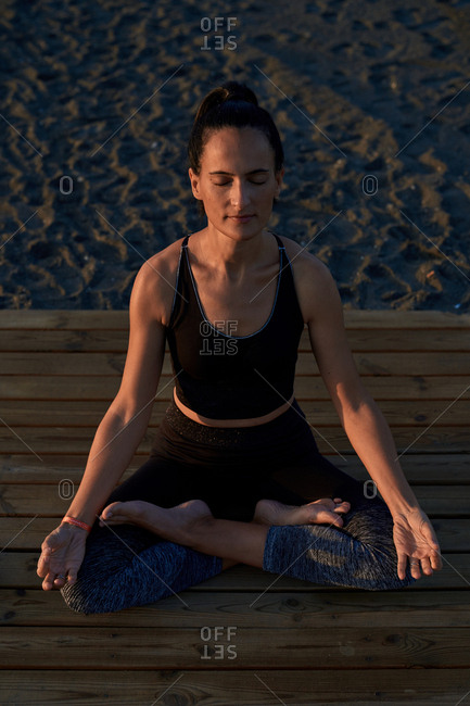 From above barefoot female in sportswear sitting in lotus pose on lumber path near sneakers and smartphone and meditating during yoga training on beach