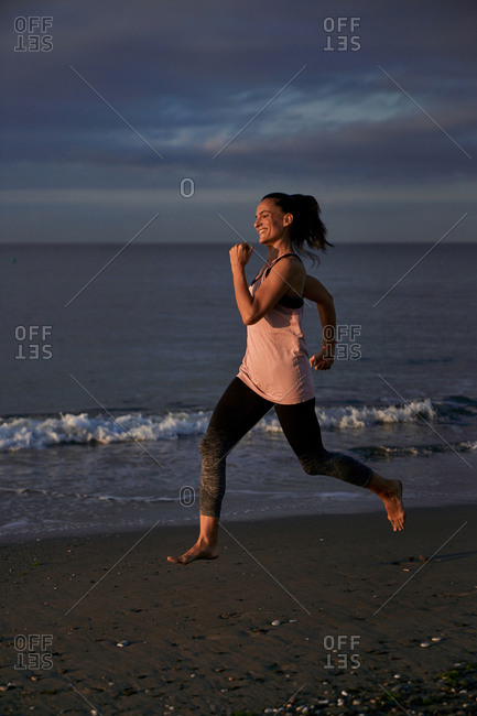 Side view of fit lady running on sandy shore near waving sea during evening workout